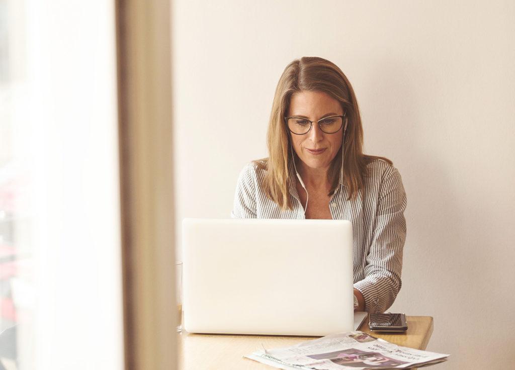 Mulher no computador à encontrar emprego e a preparar-se para entrevistas online.
