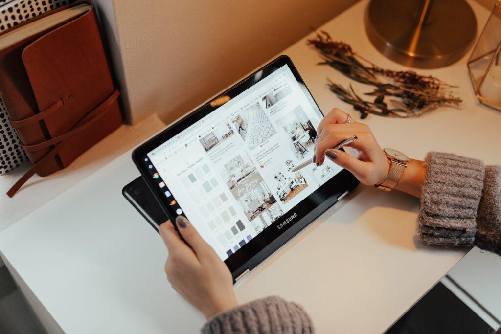Mulher que faz uma gestão de tempo eficaz a consultar o Pinterest no seu tablet.
