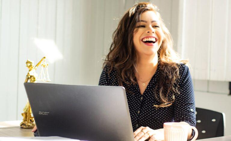 Mulher ao computador a sorrir por fazer uma gestão eficaz do seu tempo.