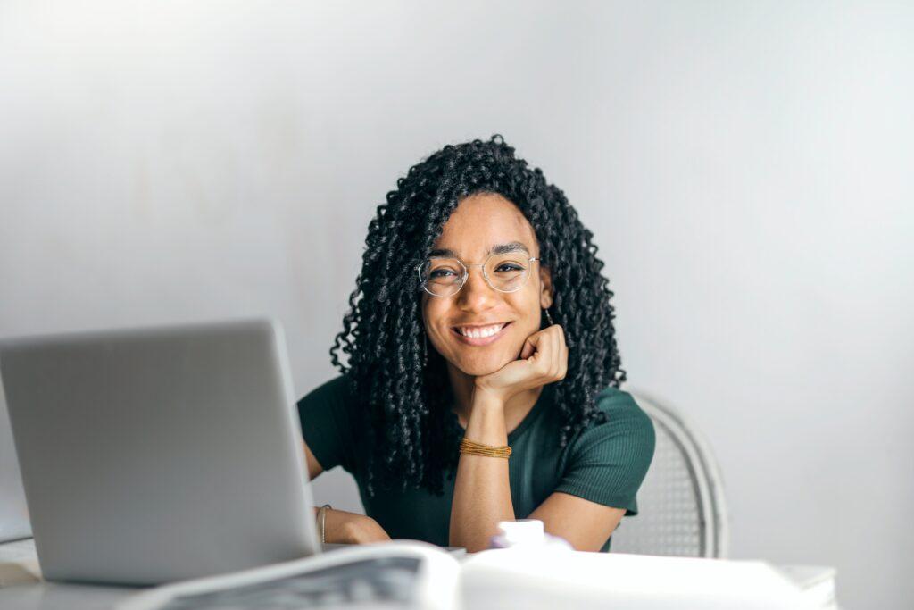 Mulher ao computador com elevada autoestima a sorrir.