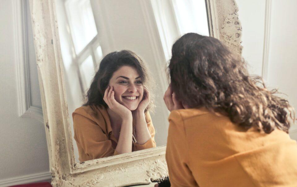 Mulher com elevada autoestima a ver-se ao espelho e a sorrir.